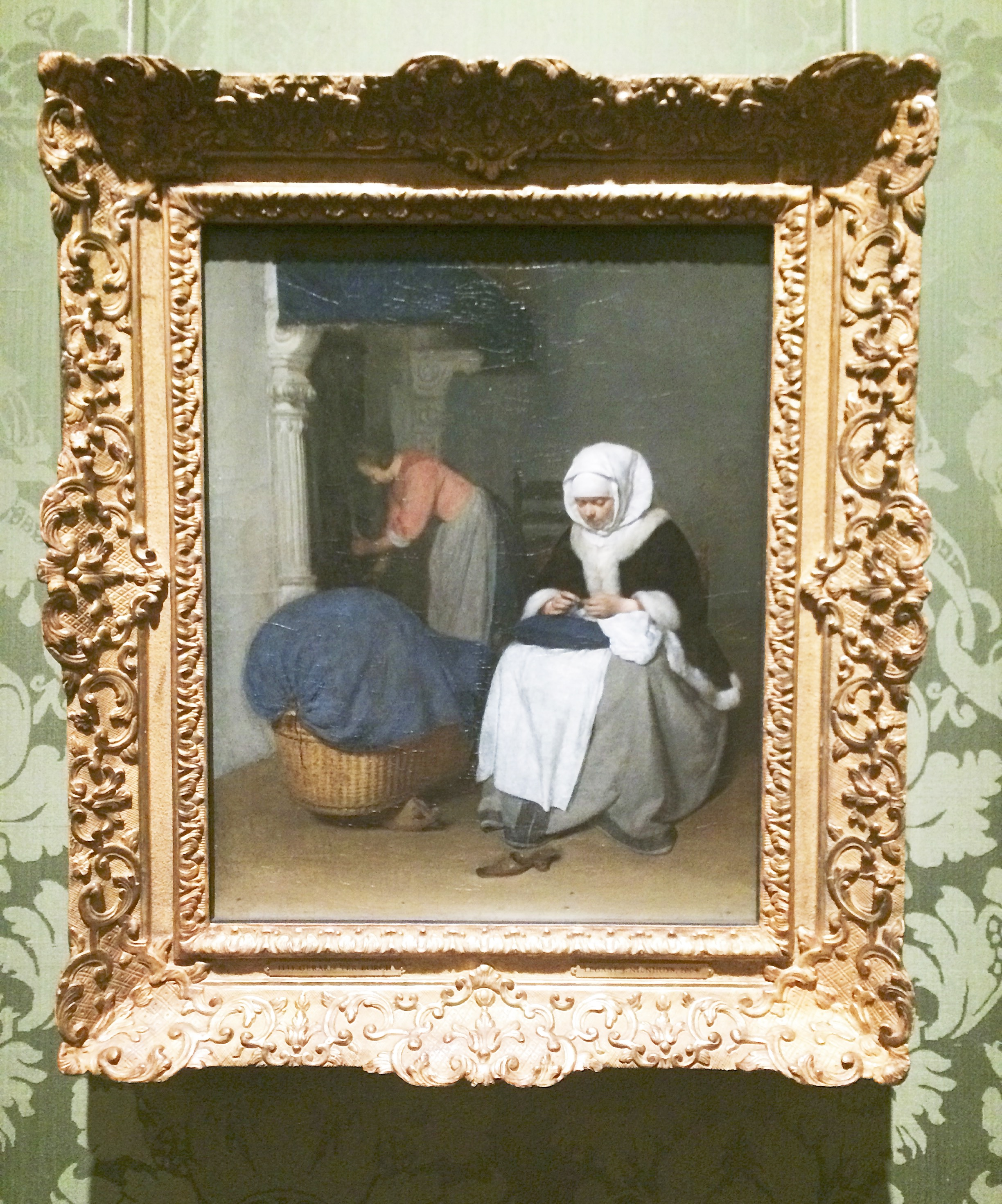 handwerkende vrouw bij een wieg